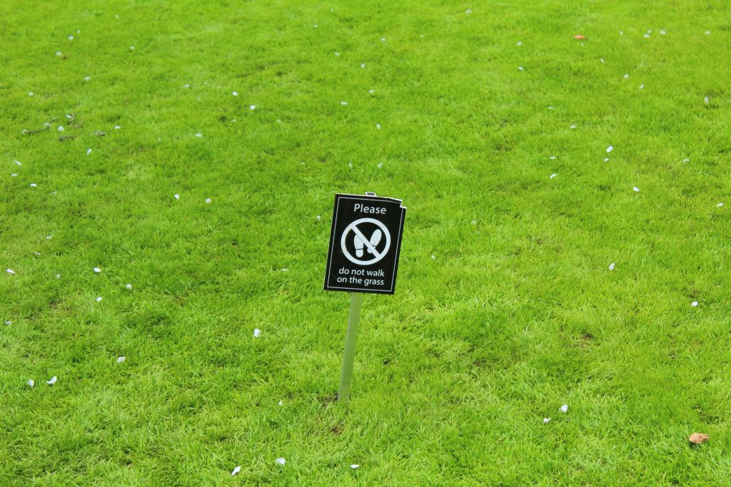 Please don't walk on the grass sign