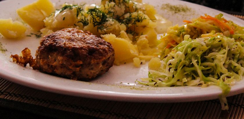 Meat balls with boiled potatoes as side dish and cabbage saldads