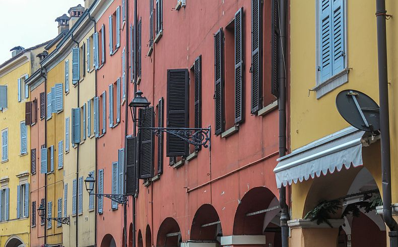 Colored residential buildings and window shutters in Modena