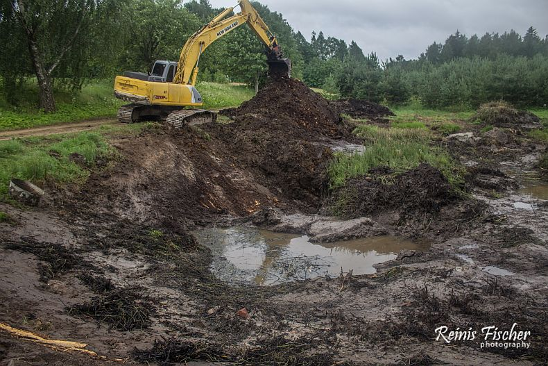 Excavator digging pond from the road side